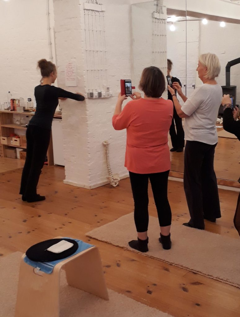 Susanne demonstriert eine Übung an der Wand